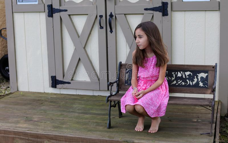 Lovely little girl at chair in the deck park with pink dress during summer in Michigan. Thinking expression stock photos