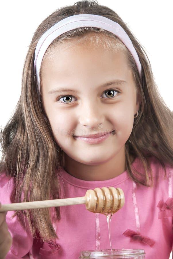 Lovely little girl eat honey royalty free stock image