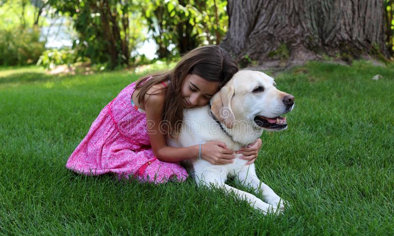 Lovely little girl with her best dog friend at park during summer in Michigan. Best friends. Pet love royalty free stock photo