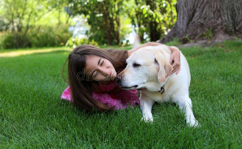 Lovely little girl with her best dog friend at park during summer in Michigan. Best friends. Pet love stock images
