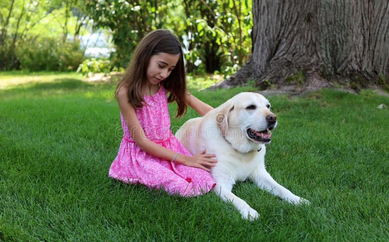 Lovely little girl with her best dog friend at park during summer in Michigan. Best friends. Pet love royalty free stock image