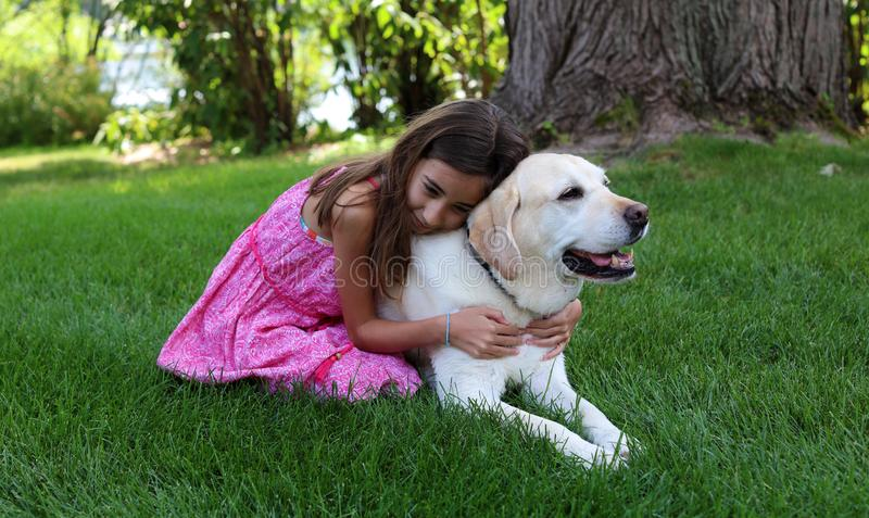Lovely little girl with her best dog friend at park during summer in Michigan. Best friends. Pet love stock photo