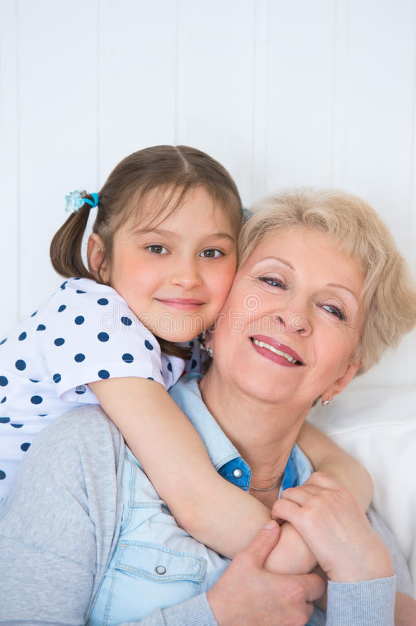 Lovely little girl with her grandmother. Having fun and happy moments together at home stock images