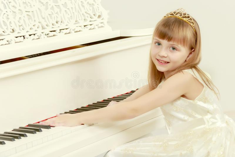 A girl is posing near a white grand piano. royalty free stock images