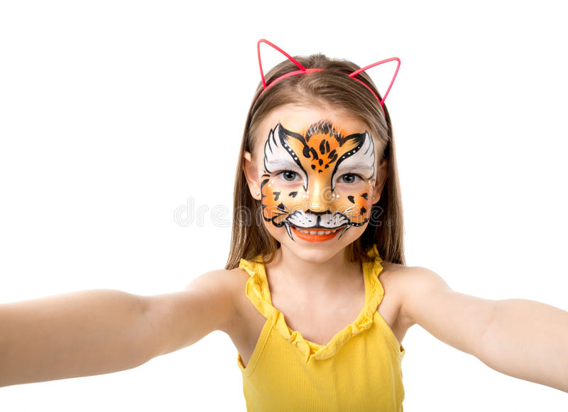 Lovely little girl with painted face making selfie. Lovely little girl with colorful painted face like tiger making selfie royalty free stock photos