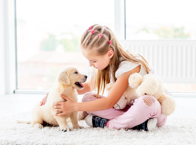 Little girl petting retriever puppy. Lovely little girl petting retriever puppy in house royalty free stock photography