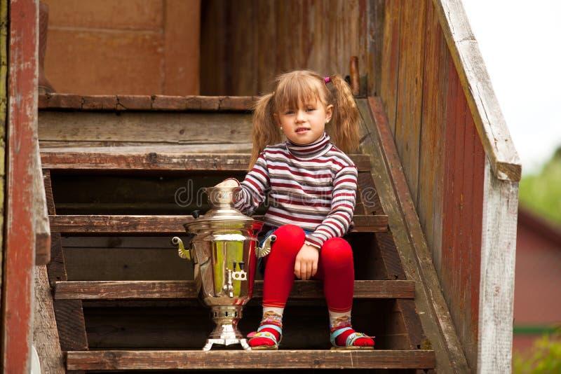Download Lovely Little Girl Posing Sitting Near The Russian Samova Stock Photo - Image: 28769674