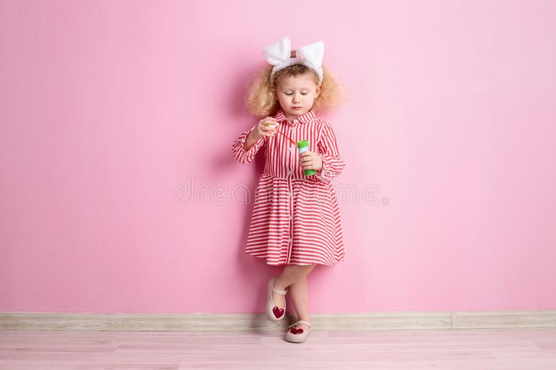 Lovely little girl in a striped red and white dress and bunny ears on her head inflates soap bubbles standing against a royalty free stock photos