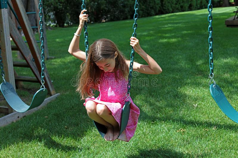 Lovely little girl at swings in the park with pink dress during summer in Michigan stock photo