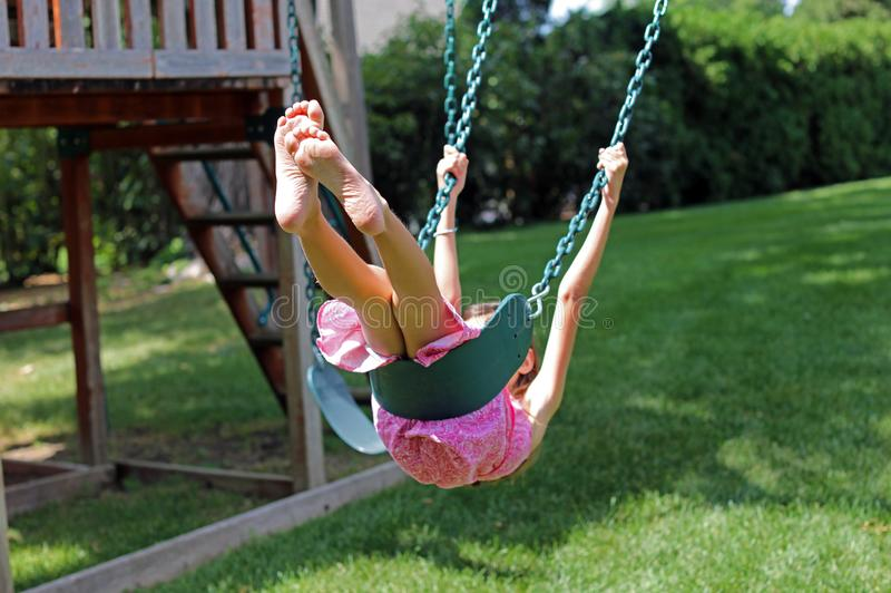 Lovely little girl at swings in the park with pink dress during summer in Michigan stock images