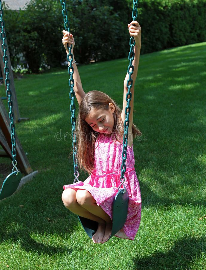 Lovely little girl at swings in the park with pink dress during summer in Michigan. Best friends royalty free stock photography