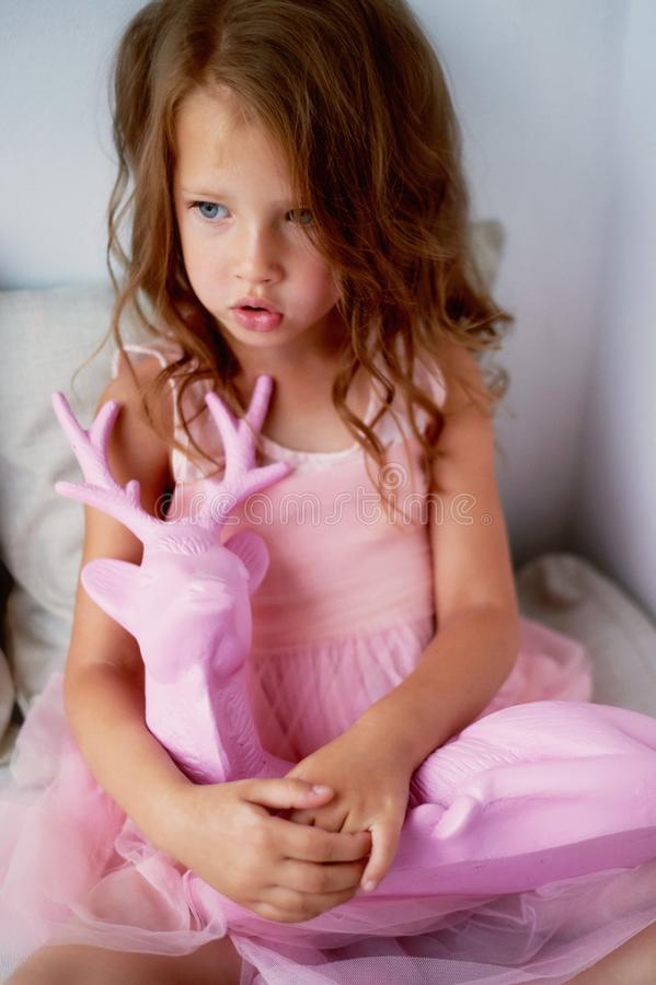 A lovely little girl 4 years old in a pink dress plays with pink deer.The atmosphere of childhood stock photos