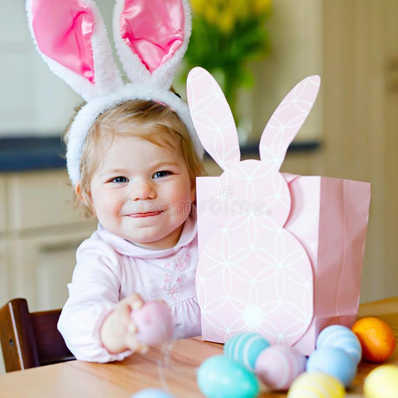 Lovely little toddler girl wearing Easter bunny ears playing with colored pastel eggs. Happy baby child unpacking gifts royalty free stock images