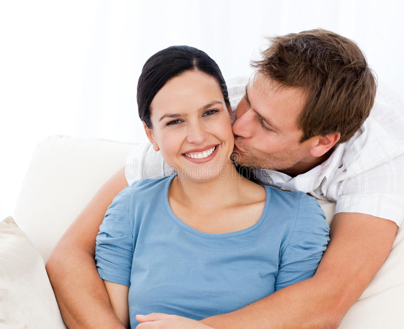 Lovely man kissing his girlfriend. While relaxing on the sofa at home royalty free stock photography