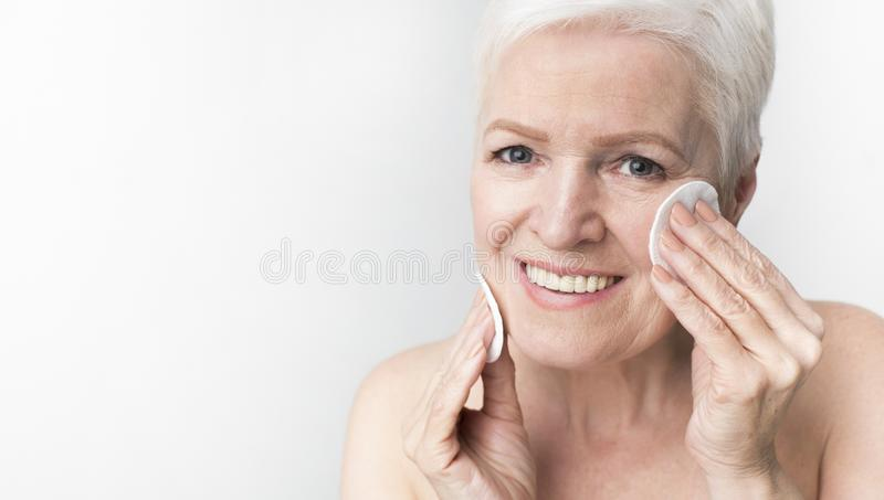 Lovely mature woman using cotton pad with micellar water royalty free stock image