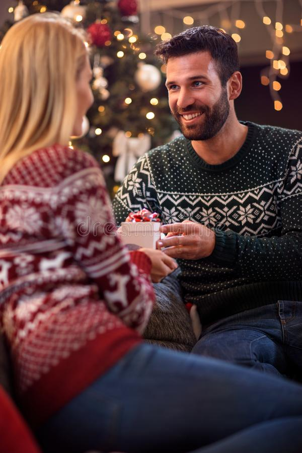 Lovely man giving Christmas gift to happy young woman royalty free stock images