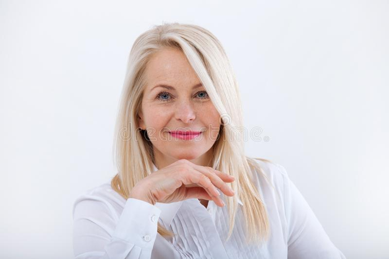Lovely middle-aged blond woman with a beaming smile sitting at office looking at the camera stock photography