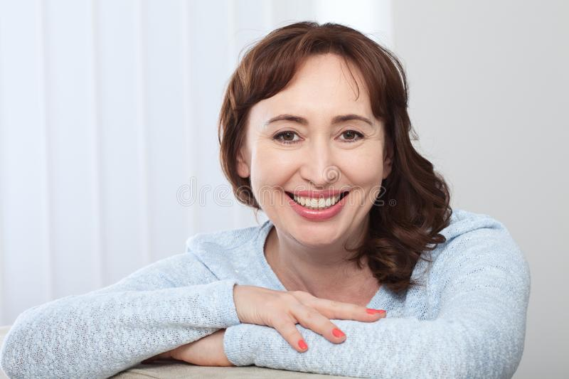 Lovely middle-aged brunette woman with a beaming smile sitting on a sofa at home looking at the camera royalty free stock photo