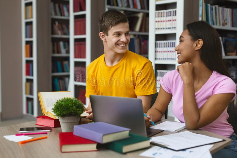 Mixed race couple of students making homework at library. Lovely mixed race couple of cheerful students making homework at library, free space stock image