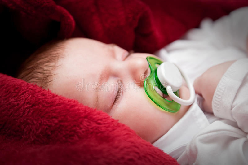 Lovely 3 months baby sleeping on bed covered with red blanket stock photo