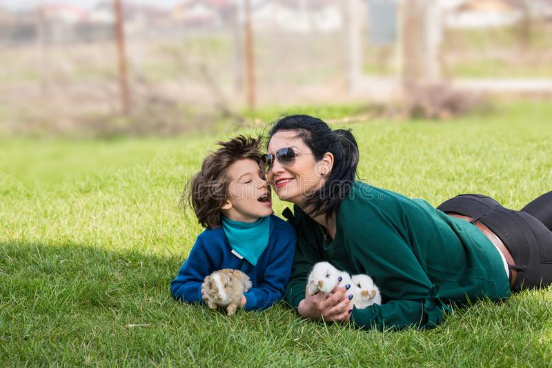 Lovely mother and son with bunnys in grass. Lovely mother and her son having fun in garden and holding little bunnys royalty free stock photography