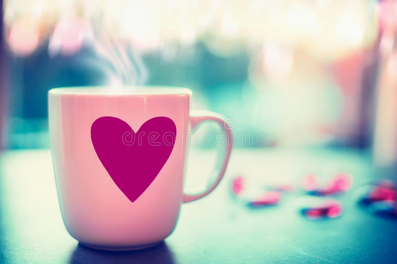 Lovely mug with pink heart on window sill at evening nature background with bokeh, front view. Love symbol or Valentines day. Concept stock photography