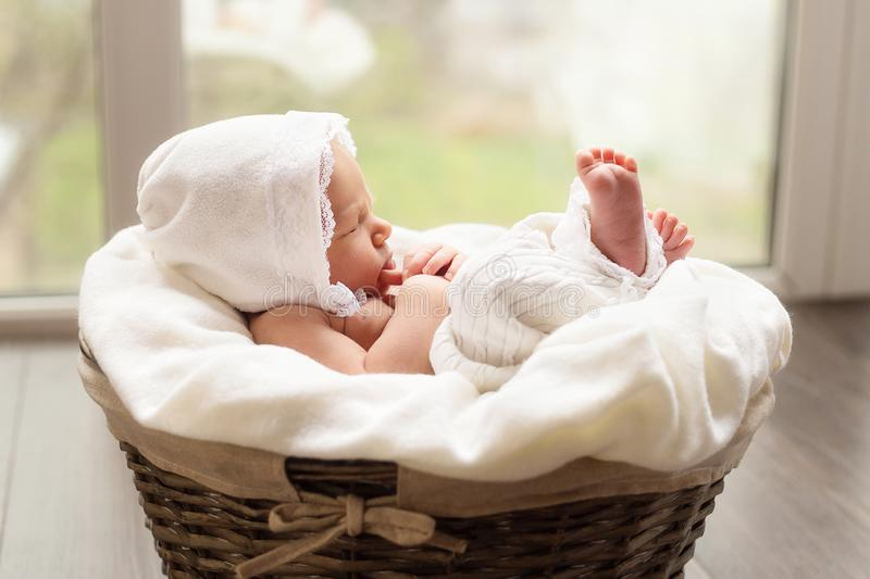 Lovely newborn baby girl is sleeping in the basket. Vintage look of a child stock image