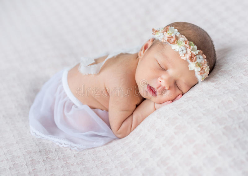 Lovely newborn girl sleeping on her stomach. Lovely newborn girl with headband sleeping on her stomach and hands under her head, covered with white shawl royalty free stock photo