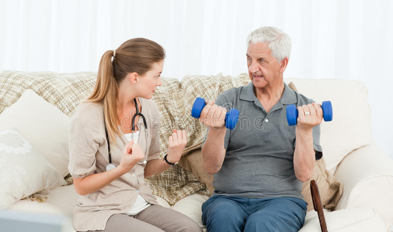 Lovely nurse helping her patient to do exercises stock image