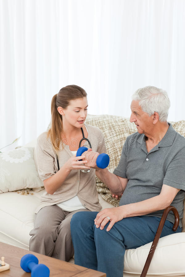Lovely Nurse Helping Her Patient To Do Exercises Stock Photography