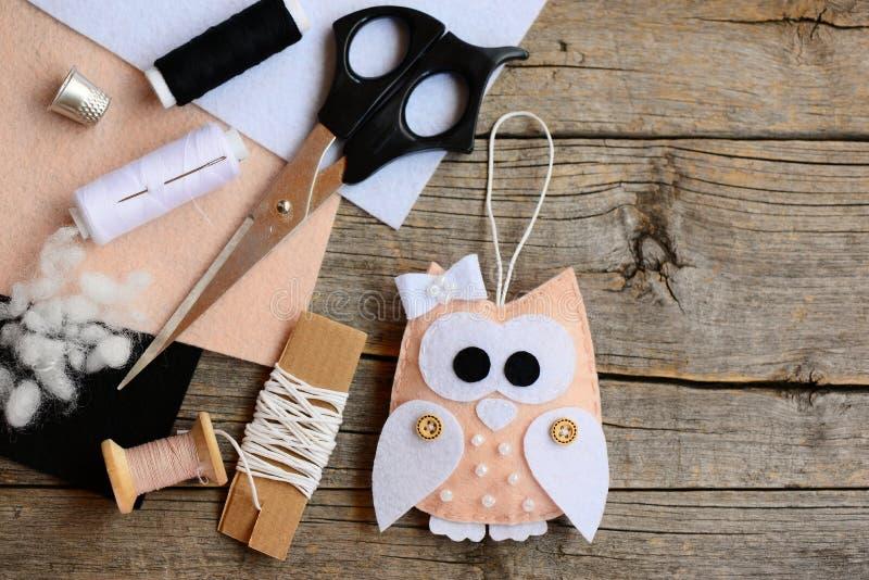 Lovely owl Christmas tree ornament made from felt. Scissors, thread, needle, thimble, felt sheets, waxed cord stock photos