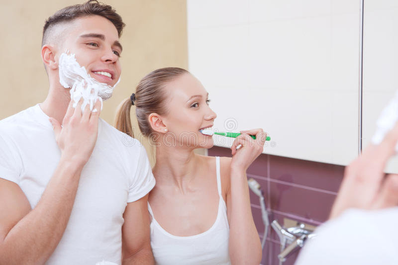 Lovely pair doing morning routine. Everything together. Lovely pair doing morning routine together in front of mirror in bathroom royalty free stock photos