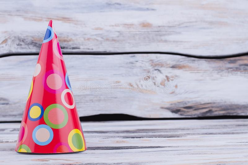Lovely paper cone Birthday party hat. Patterned Bithday party cap on vintage wooden background with text space. Happy Birthday background royalty free stock photo
