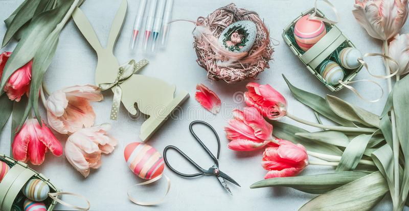 Lovely pastel color Easter flat lay with eggs, bird eggs, feathers and tulips, scissors and tags. Easter greeting preparation, top stock photography