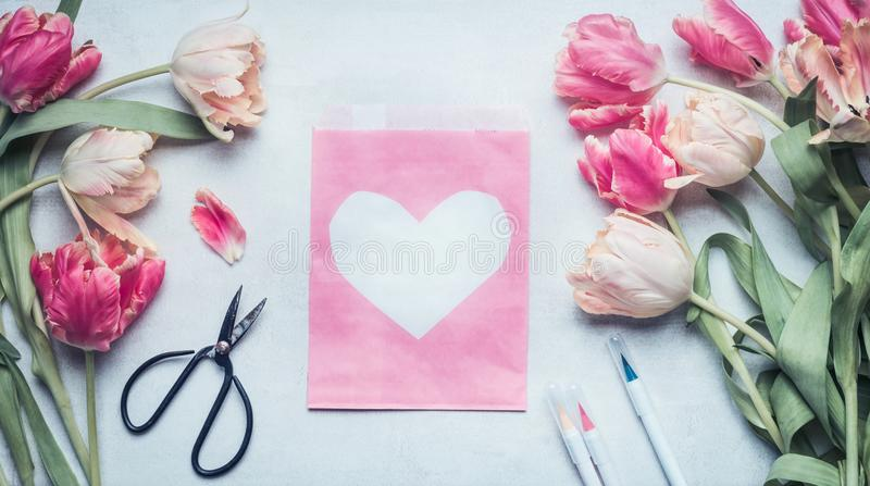 Lovely pastel color spring mock up with tulips, scissors , markers and pink pack paper bag with heart royalty free stock images