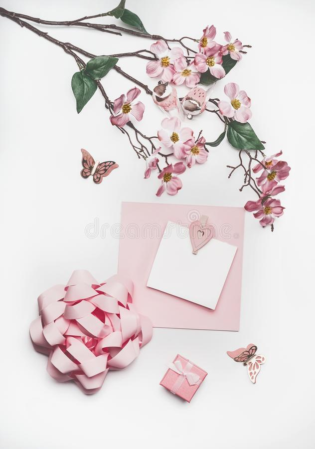 Lovely pastel pink greeting card mock up with blossom decoration, hearts, little gift box and bow on white desk background, top vi. Ew, flat lay. Wedding royalty free stock image