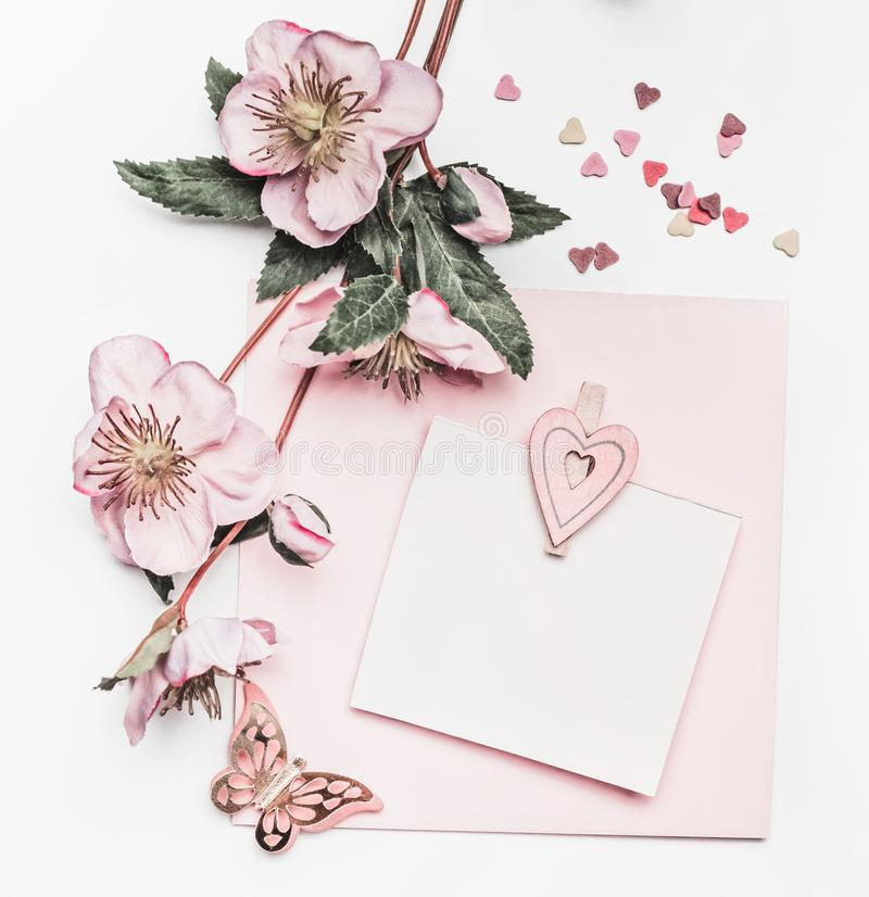 Lovely pastel pink layout with flowers decoration, ribbon, hearts and card mock up on white desk background, top view, flat lay. W royalty free stock image