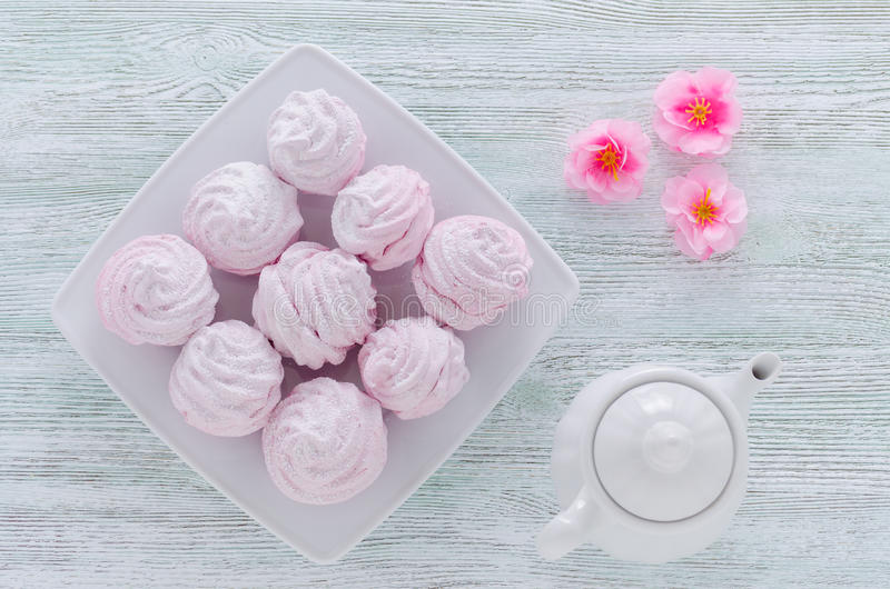 Lovely pastel rose meringues, zephyrs, marshmallows and a coffee pot, flowers on the wooden vintage table stock photography