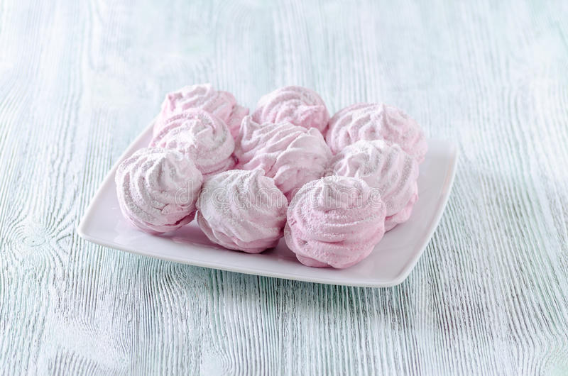 Lovely pastel rose meringues, zephyrs, marshmallows on the wooden vintage table royalty free stock photos