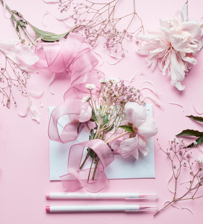 Lovely pink Florist workspace. Beautiful flowers, envelop ,ribbon and markers pencil on pastel background, top view. Creative Inv royalty free stock photo