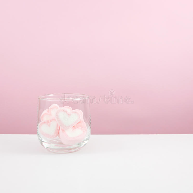 The lovely pink heart marshmallows in small round glass stock photos