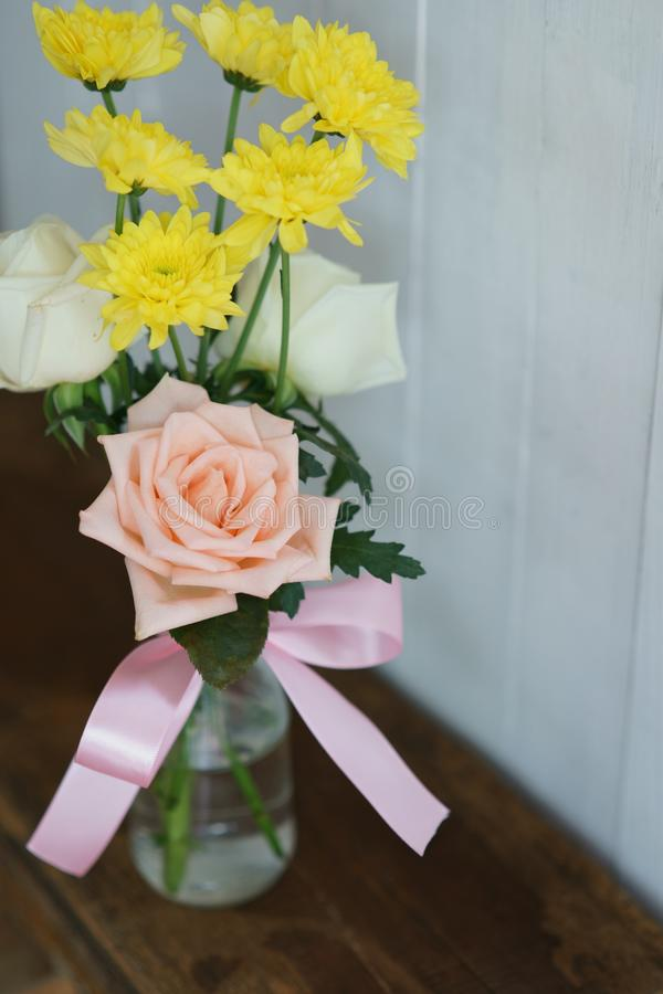Lovely pinky blossom rose in vase on wooden table with white wall background, copy space royalty free stock images