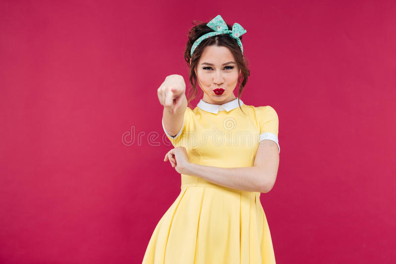 Lovely playful young woman standing and pointing on you. Lovely playful young woman in yellow dress standing and pointing on you over pink background stock photos