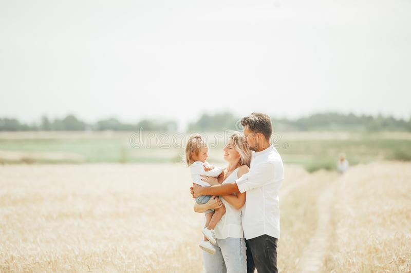 Lovely portrait of a young beautiful family in wheat field on warm and sunny summer day stock photos
