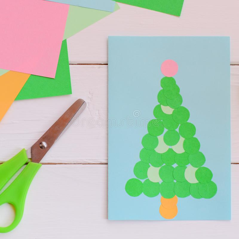 Lovely postcard with a Christmas tree. Christmas greeting card made from colored paper using glue. Simple children handicrafts. Christmas card idea. Easy royalty free stock images