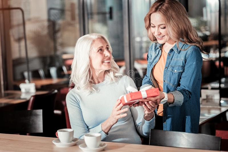 Kind attentive woman giving a present to her cheerful senior granny stock photography