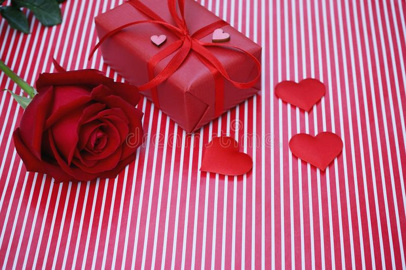Lovely red color gift box decorated with mini red heart figure and beautiful rose flower, sweet valentine present concept,. Background and texture for valentine royalty free stock photo