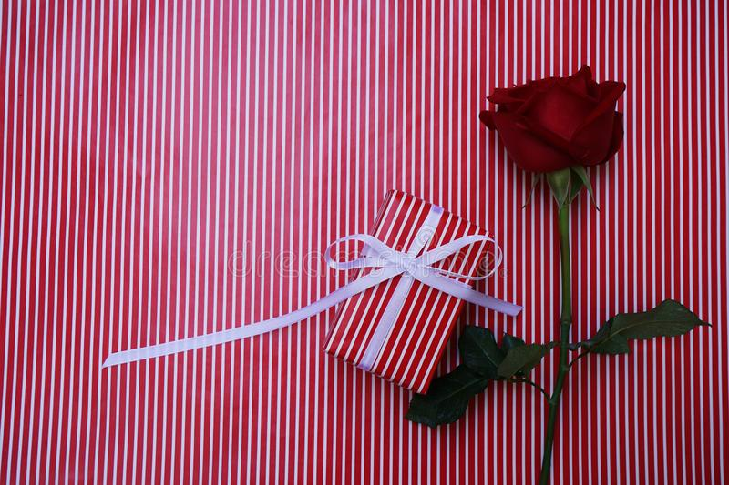 Lovely red color gift box decorated with mini red heart figure and beautiful rose flower, sweet valentine present concept,. Background and texture for valentine stock photo