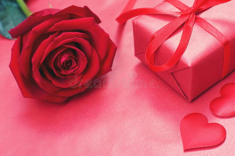 Lovely red color gift box decorated with mini red heart figure and beautiful rose flower, sweet valentine present concept,. Background and texture for valentine stock image