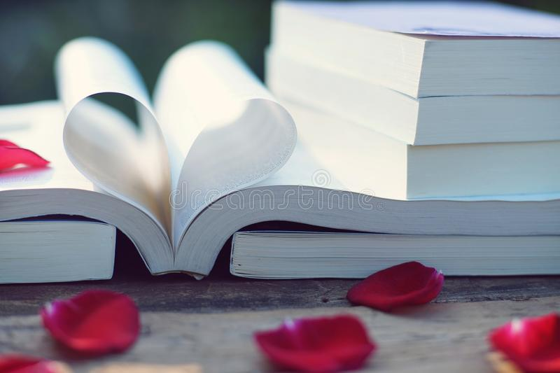 Lovely red color rose petals on book roll into heart shape with blur green garden background, soft color tone, sweet valentine. Concept, copy space royalty free stock photo